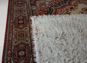 Two carpets on a painted wood floor